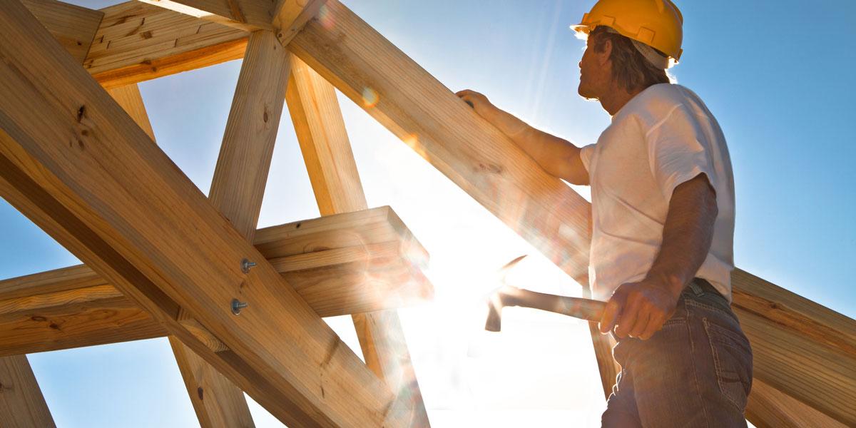 Roofer holding hammer, sun in background.