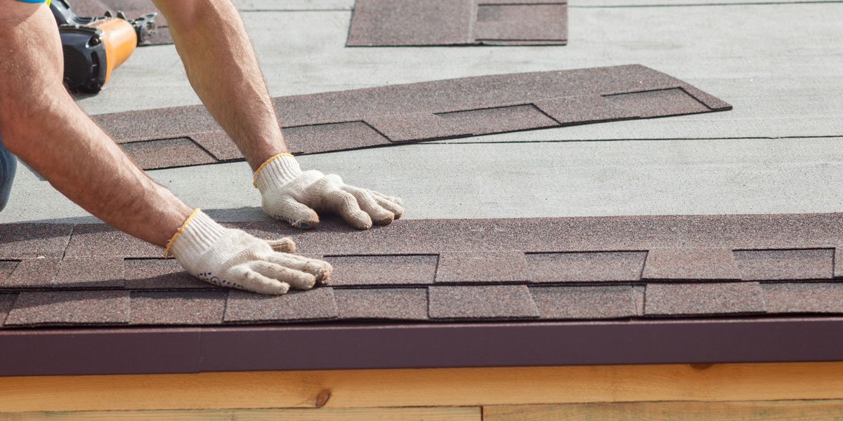 Close up of roofer replacing tiles on a roof