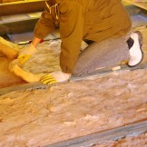 Construction worker thermally insulating house attic with glass